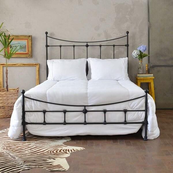 O jogo de cama branco se destaca sobre a cama com cabeceira de ferro