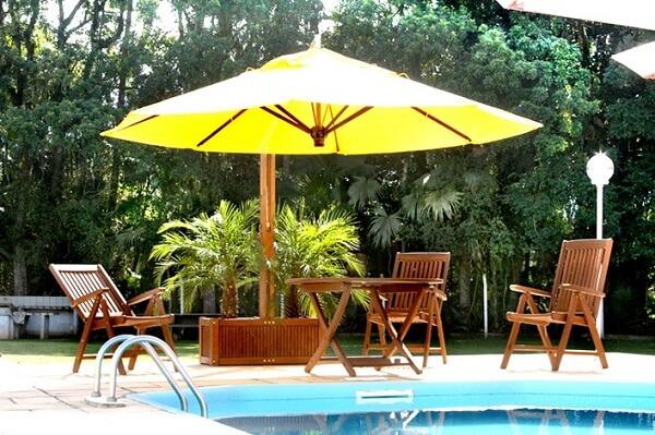 O ombrelone de madeira com floreira serve de apoio para o cultivo de flores artificiais e naturais