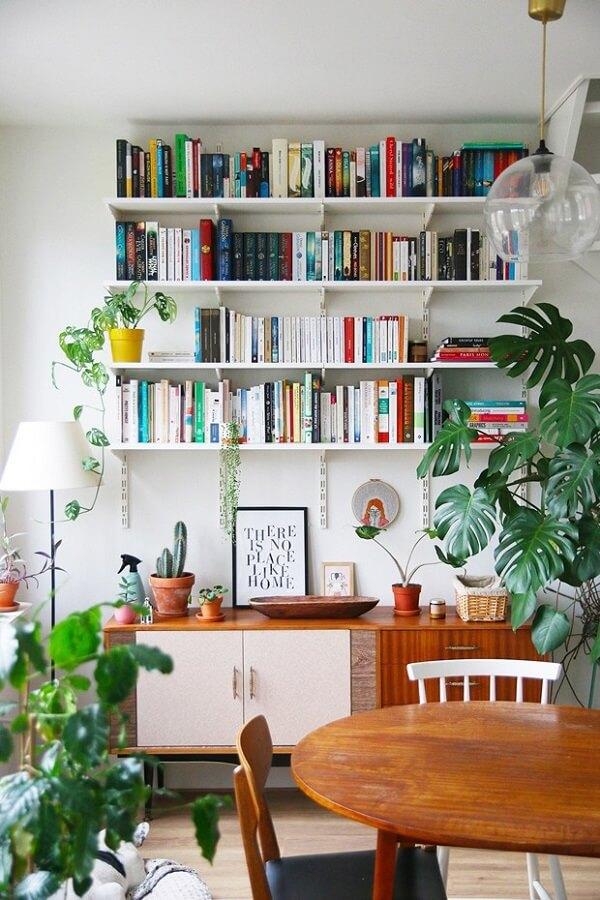 O verde das plantas traz um toque especial para o ambiente com estante branca