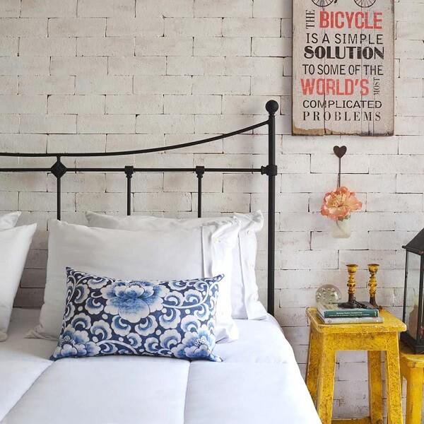 Parede de tijolinho branco e cabeceira de ferro para cama box decoram o quarto