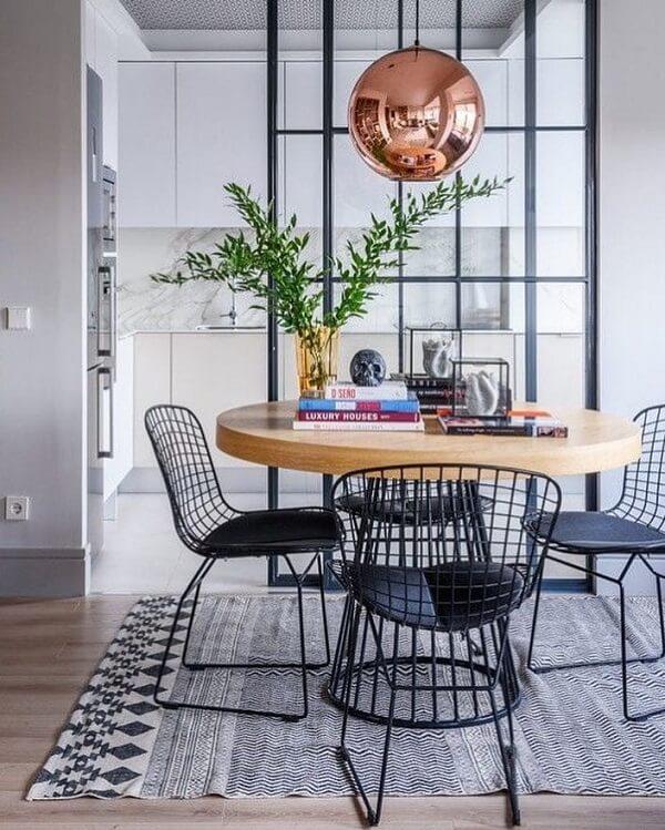 Sala de jantar sofisticada com mesa redonda e cadeira Bertoia preta