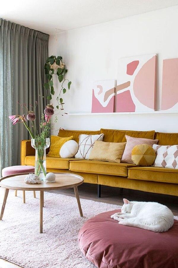 Sofá amarelo e mesa de centro retrô redonda decoram o cômodo
