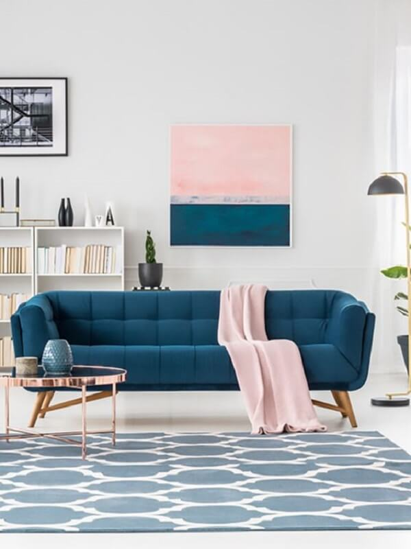 Sofá azul, manta rosa e mesa de centro retrô redonda com acabamento delicado decoram a sala