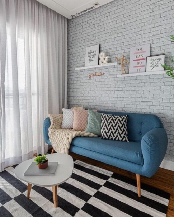 Sofá, mesa de centro estilo retrô e tijolinho branco complementam a decoração do ambiente