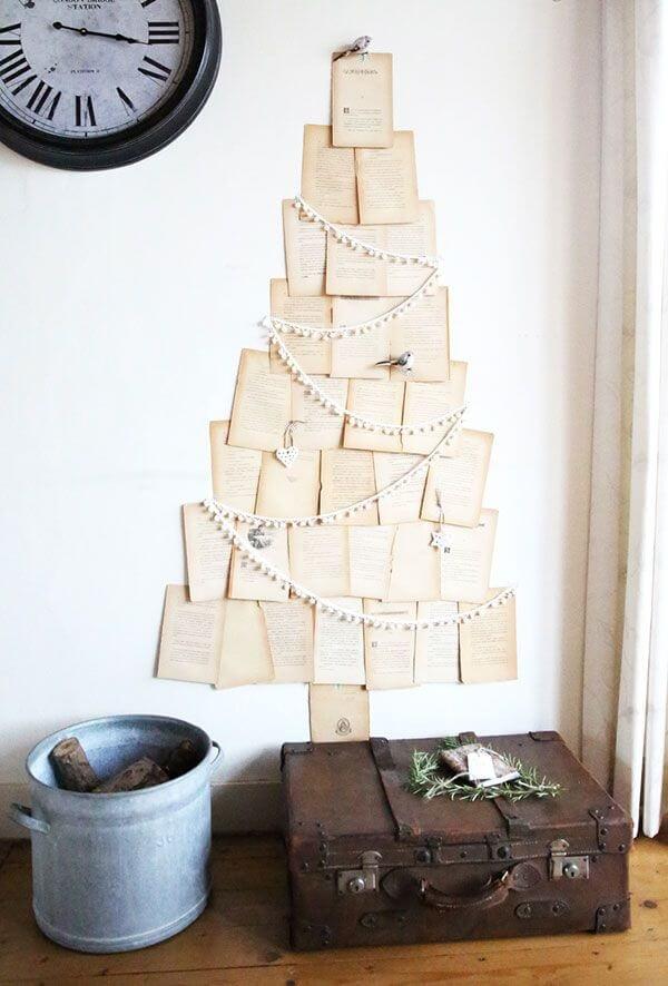 Folhas de livro formando árvore de natal diferente na parede