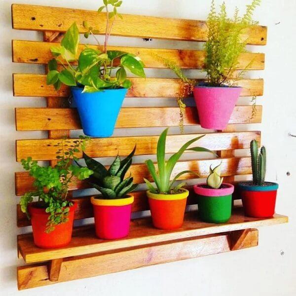 Vasos coloridos decoram a prateleira de pallet para plantas