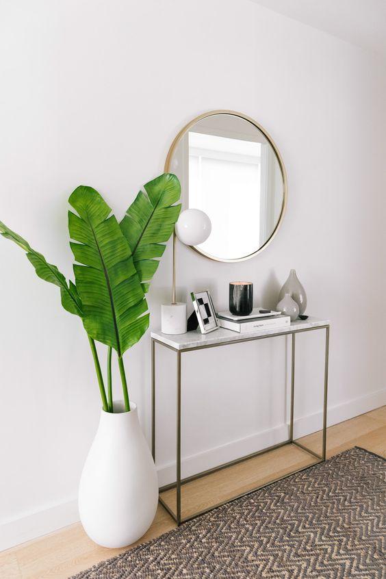 Aparador para corredor decorado com plantas e espelho