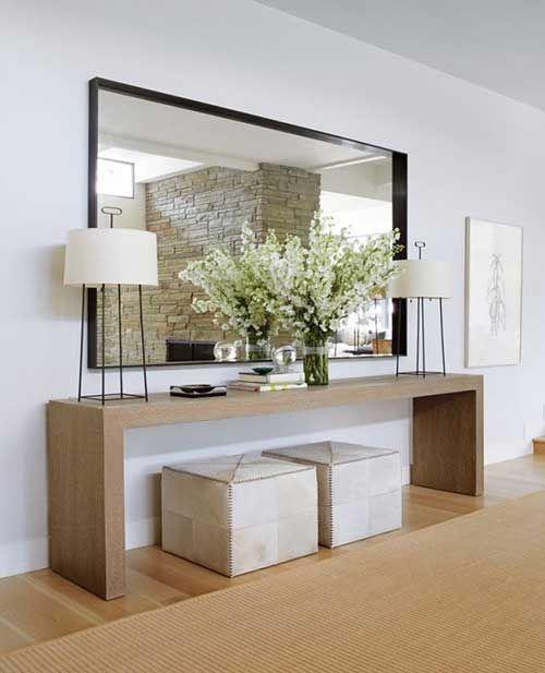 Aparador para corredor feito de madeira com espelho grande acima e vasos de flores decorando