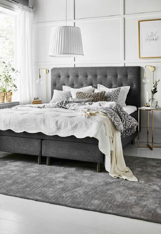 cabeceira estofada cinza para decoração de quarto com mesa de cabeceira redonda e luminária de parede dourada  Foto El Mueble