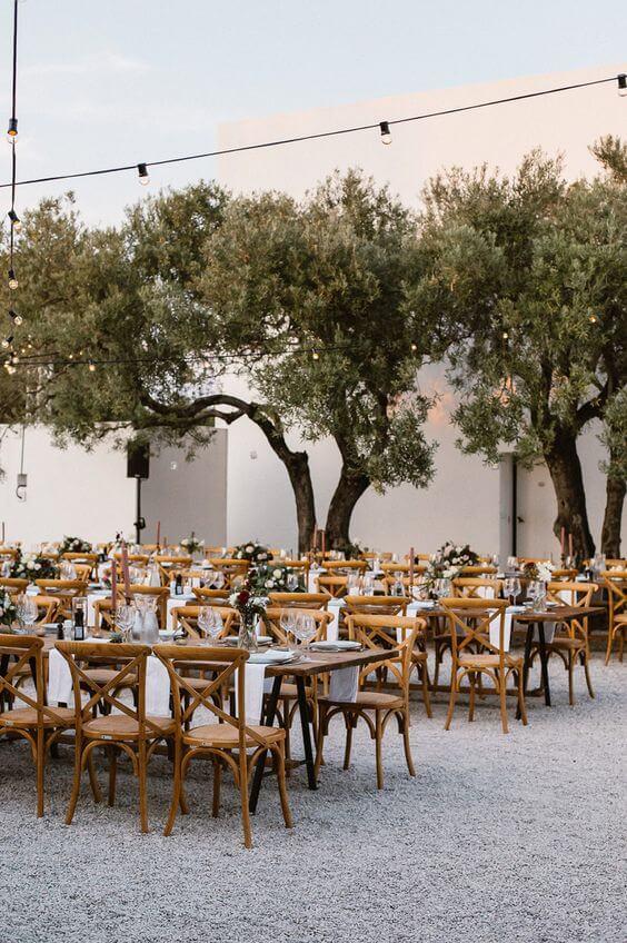 Festa decorada com mesas coletivas e cadeira paris