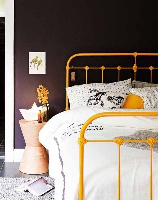 Cama de ferro amarelo no quarto moderno