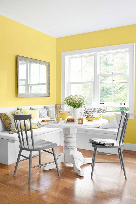 Mesa de canto alemão com parede amarela e móveis brancos