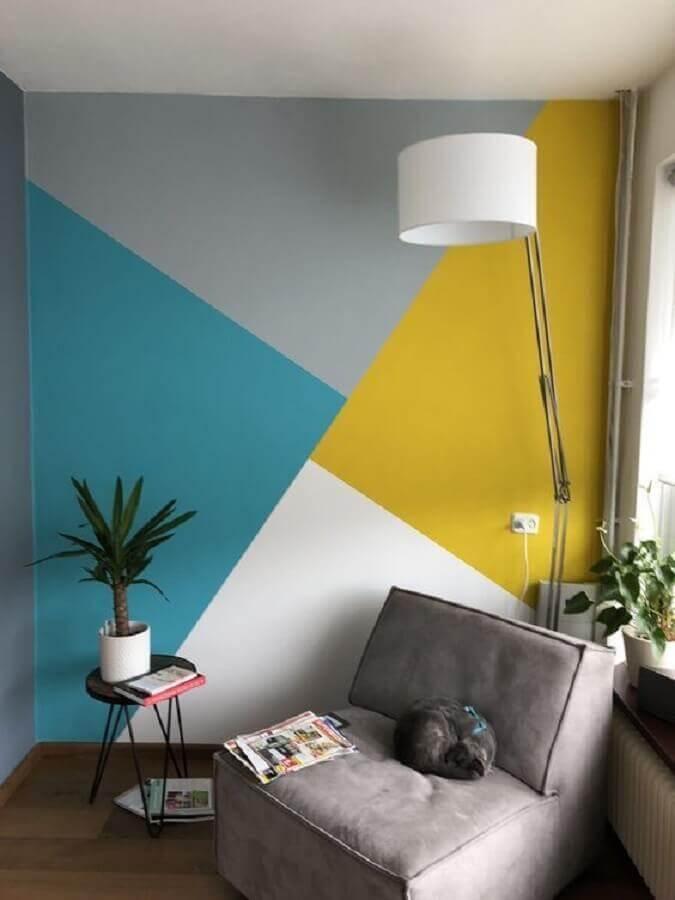 cantinho de leitura decorado com parede com pintura geométrica e poltrona cinza  Foto Pinterest