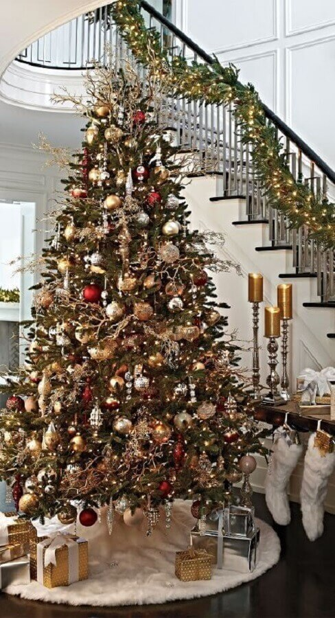 house decorated with large and full Christmas tree next to staircase Photo Warehouse Home