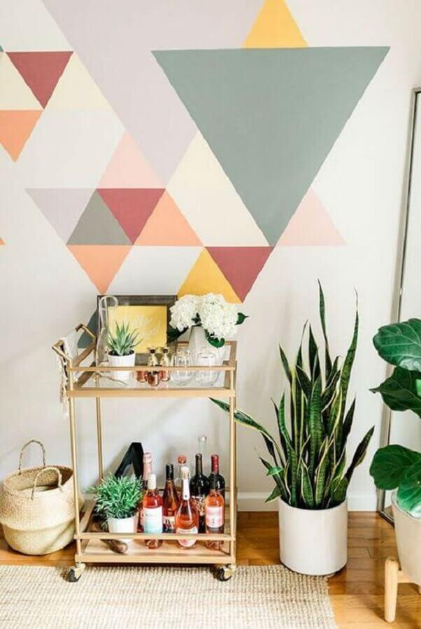 decoração colorida com pintura de parede geométrica e carrinho bar dourado Foto iCasei