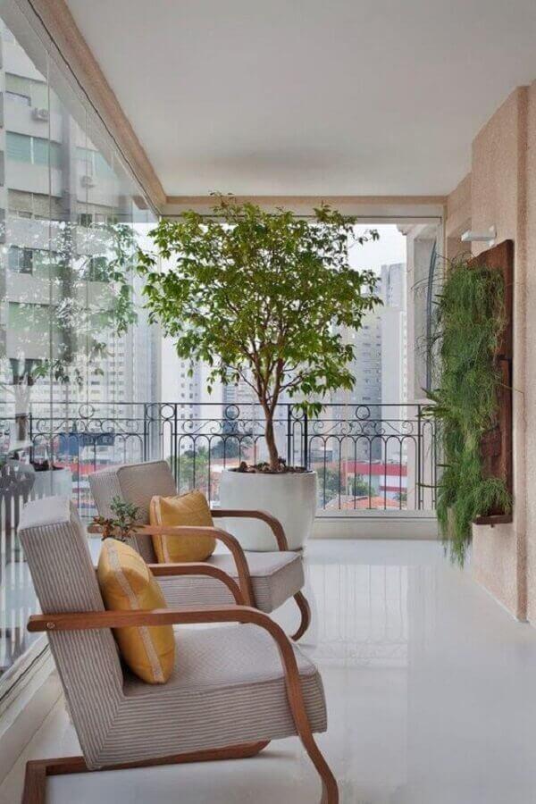 decoração com plantas para varanda ampla com poltronas de madeira  Foto Jeito de Casa