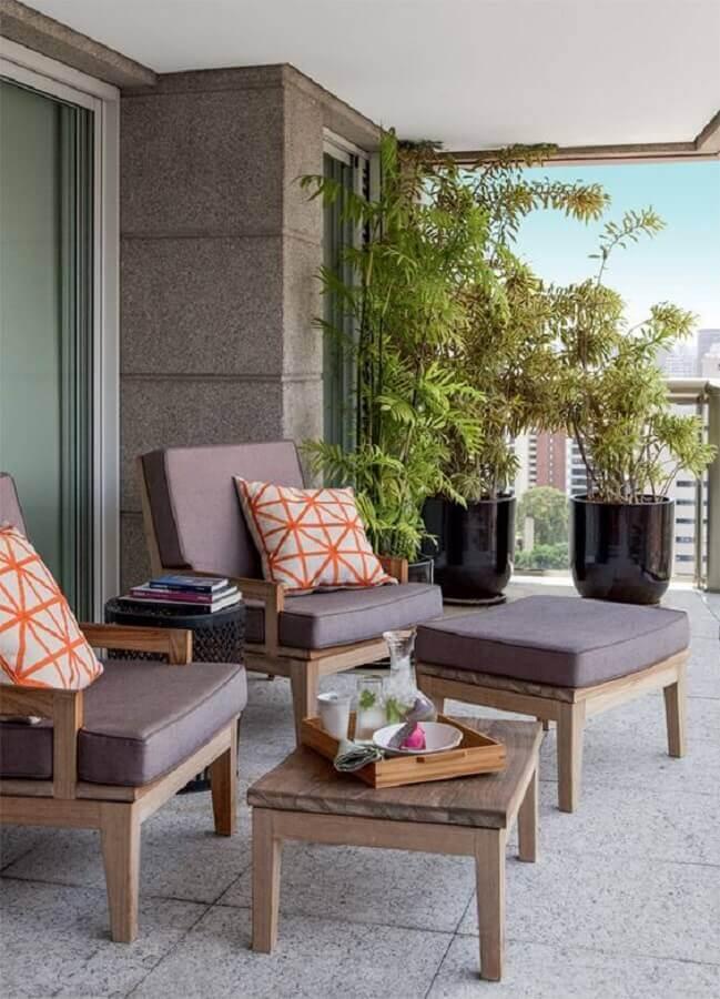 decoração com poltrona de madeira e vasos de plantas para varanda de apartamento grande Foto Jeito de Casa
