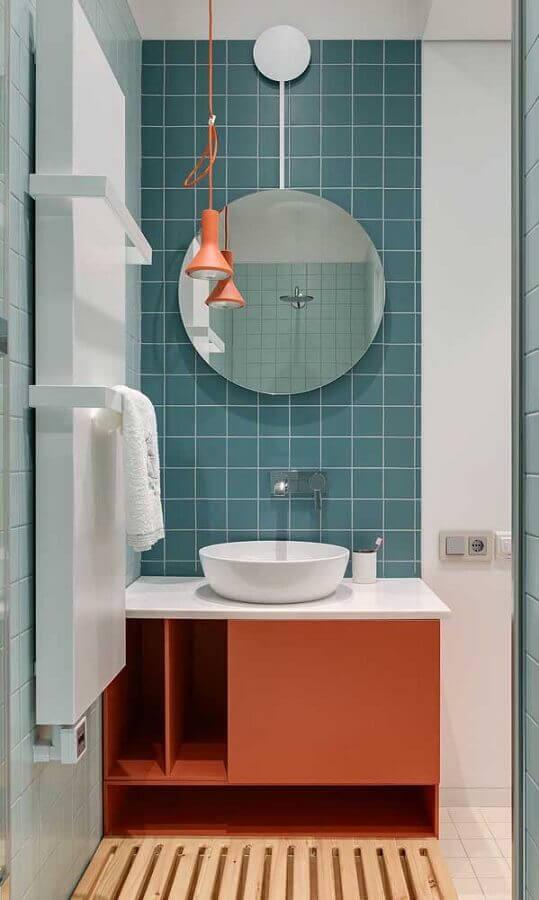 decoração com revestimento azul e pendente para bancada de banheiro com gabinete coral  Foto Apartment Therapy