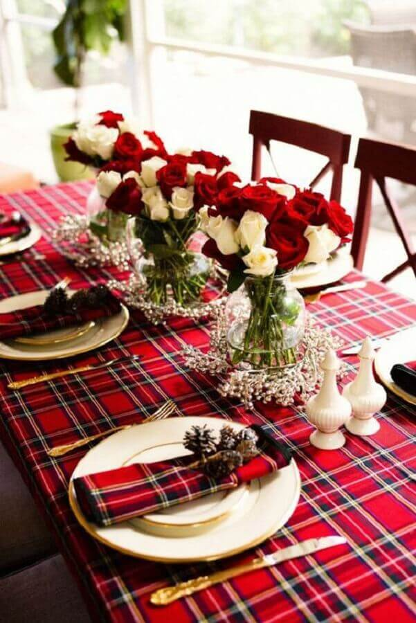 decoração de mesa natalina simples com toalha xadrez vermelha e arranjos de rosas brancas e vermelhas Foto iCasei