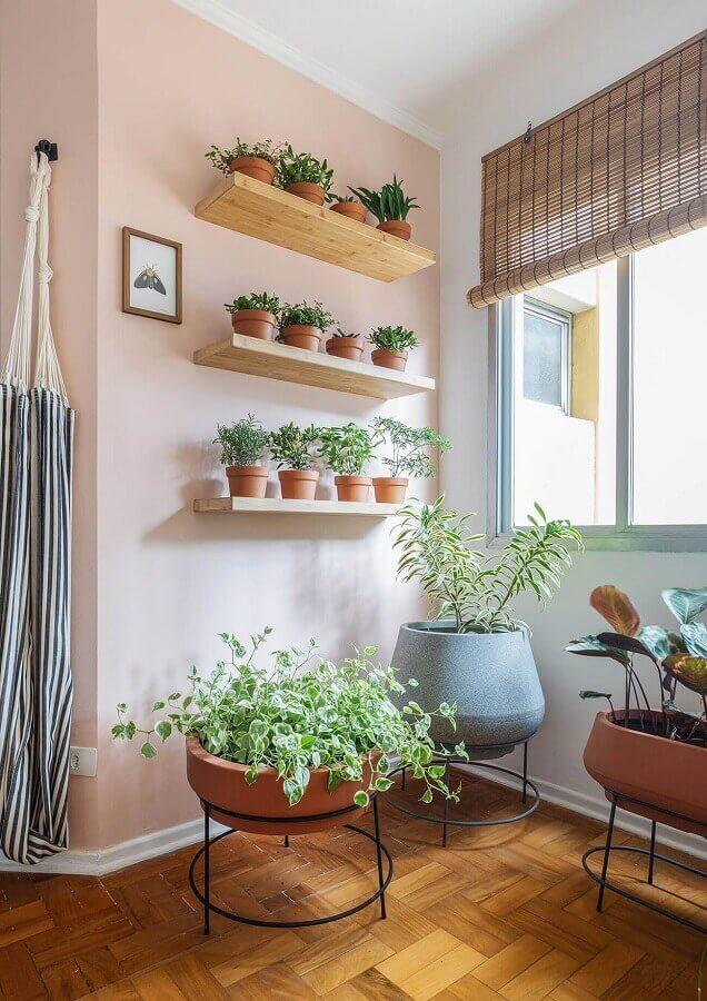 decoração de sala com parede rosa e prateleira de madeira para plantas Foto Histórias de Casa