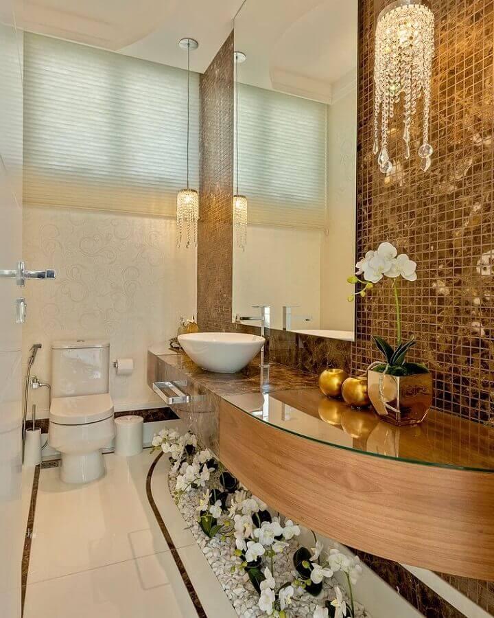 decoração sofisticada com luminária de cristal pendente para bancada de banheiro com pastilhas douradas Foto Iara Kílaris Decoradora