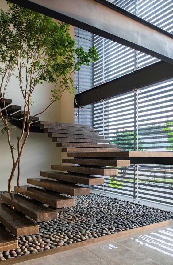 Escada de madeira decorada com pedras seixos