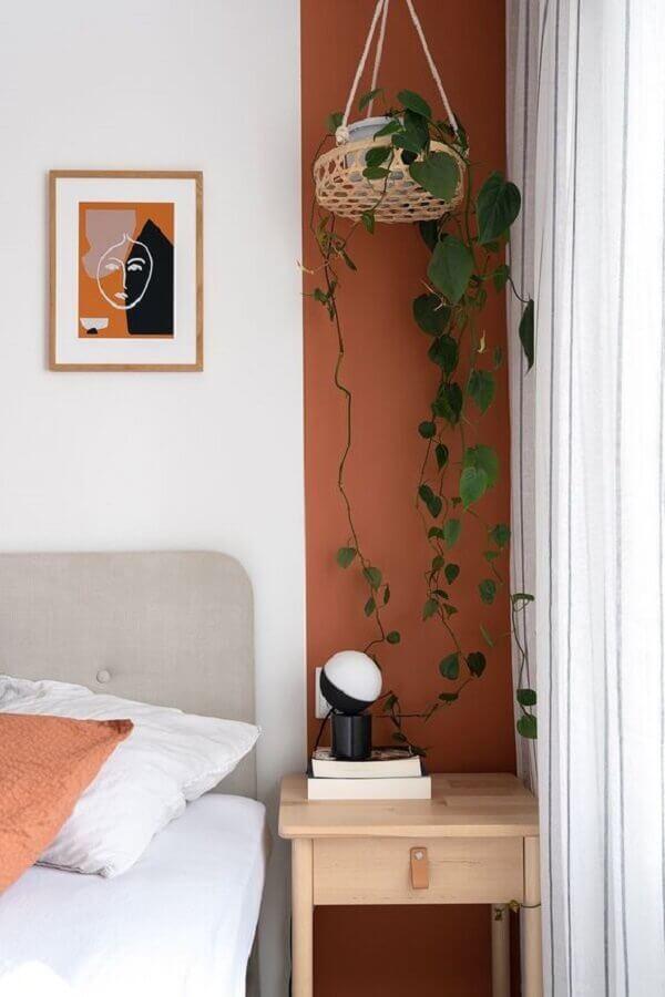 detalhe na parede em tons terrosos para quarto decorado com criado mudo madeira Foto Home Fashion Trend