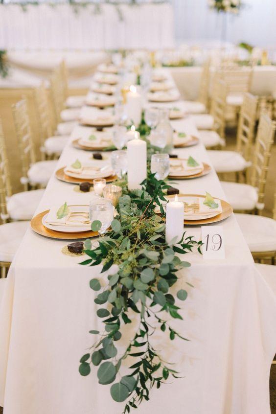Mesa simples com enfeites de natal para mesa feitos de plantas e velas brancas