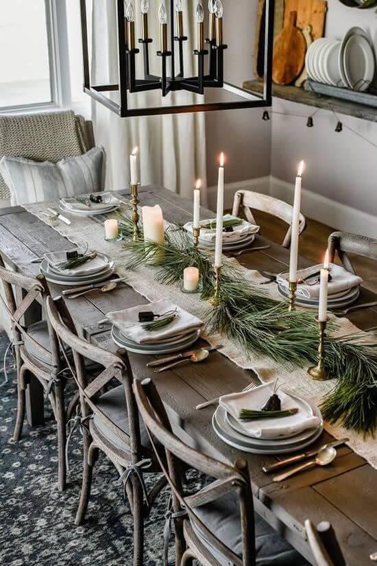 Mesa de natal simples com plantas e velas altas no castiçal