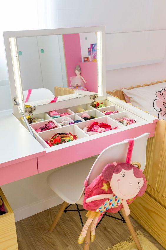 Escrivaninha e penteadeira rosa no quarto infantil