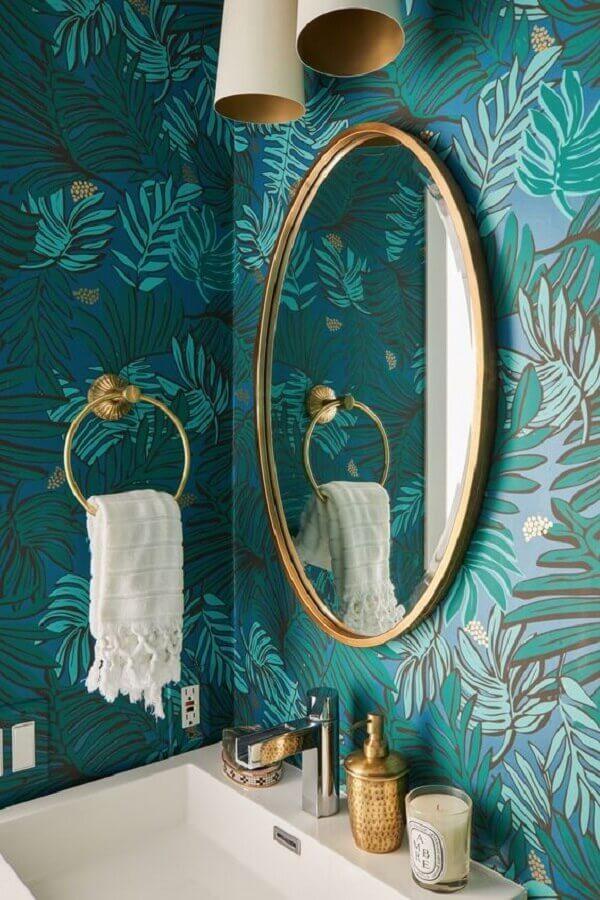 espelho redondo dourado e papel de parede para banheiro com estampa de folhagem Foto Hunker