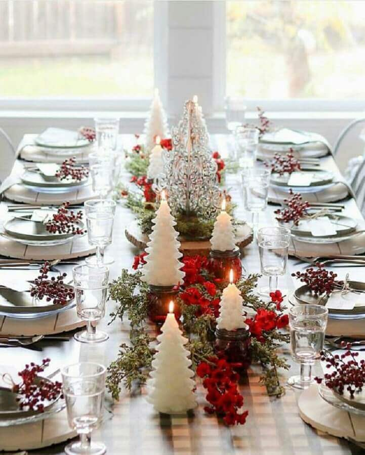 Christmas table decorated with red flowers and candles in Christmas tree shape Photo Home Fashion Trend