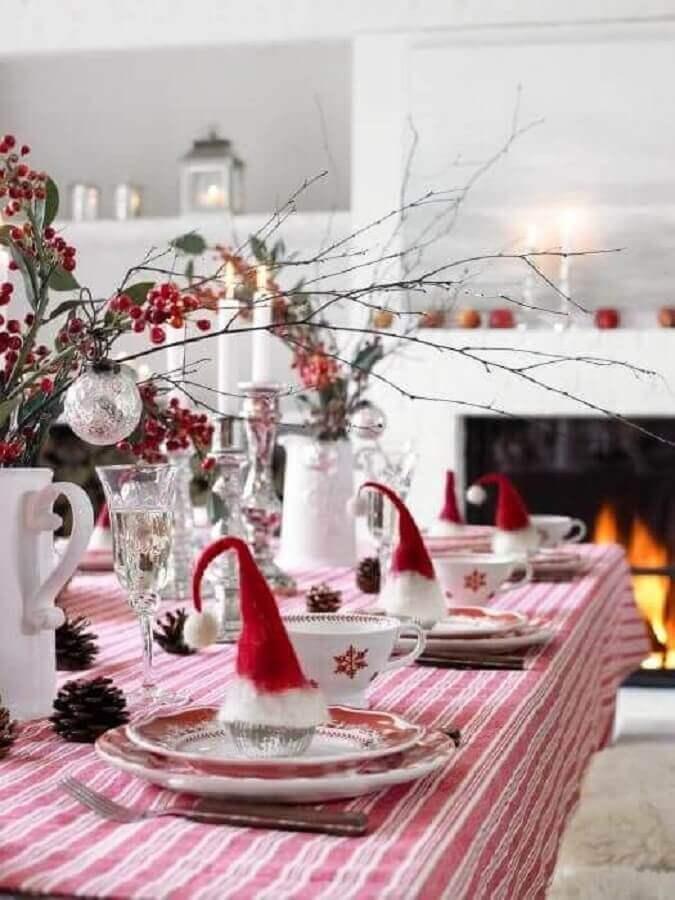 mesa natalina simples com chapeuzinho de papai Noel em cada prato Foto Pinterest
