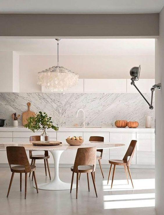 Mesa saarinen oval na sala de jantar branca com lustre moderno