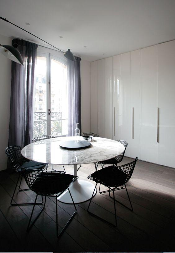 Mesa saarinen redonda e branca com cadeiras pretas