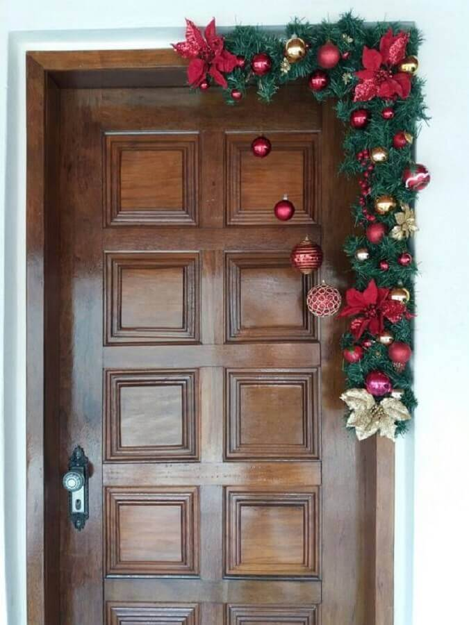 different model of Christmas ornament for door with festoon decorated with balls and Christmas flowers Photo Very Chique