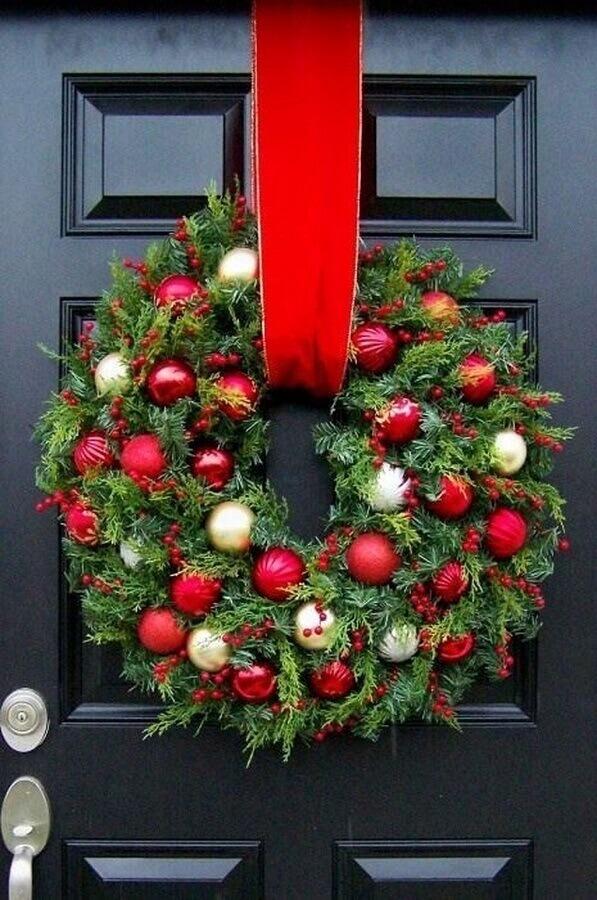 modelo tradicional de enfeite natalino para porta com guirlanda decorada com bolas de natal Foto Pinterest