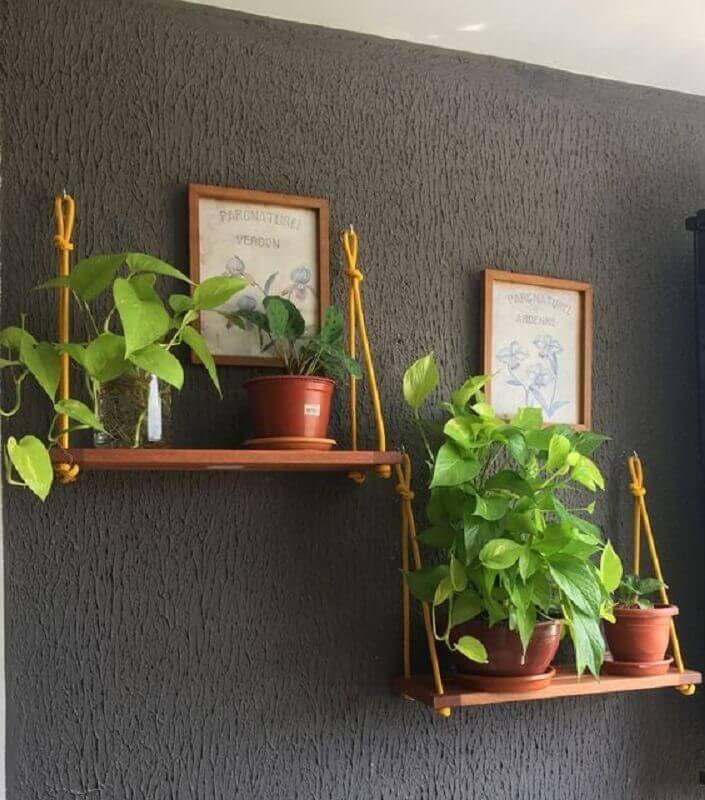 parede preta decorada com prateleira suspensa para plantas Foto Jeito de Casa