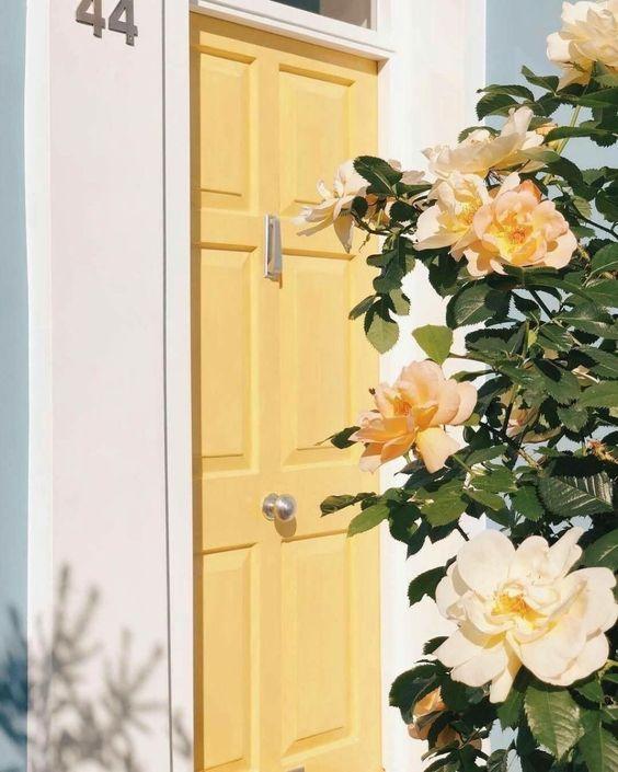 Porta amarelo pastel e flores na decoração