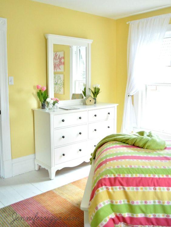 Quarto amarelo pastel com manta colorida