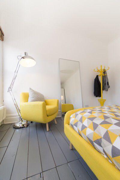 Poltrona e cama amarelo pastel no quarto clean