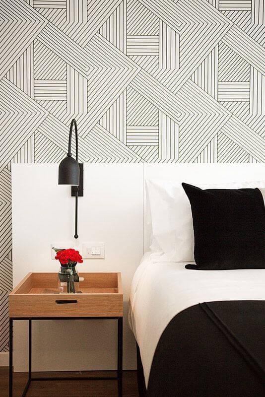 quarto branco decorado com papel de parede geométrico e luminária de cabeceira para leitura Foto Home Fashion Trend