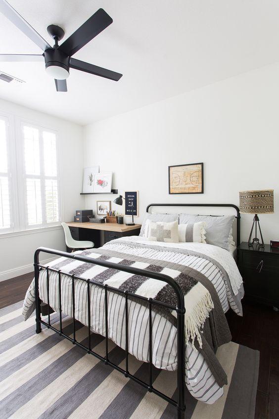 Cama de ferro preta no quarto preto e branco