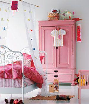 Quarto infantil com cama de ferro branca e decoração rosa