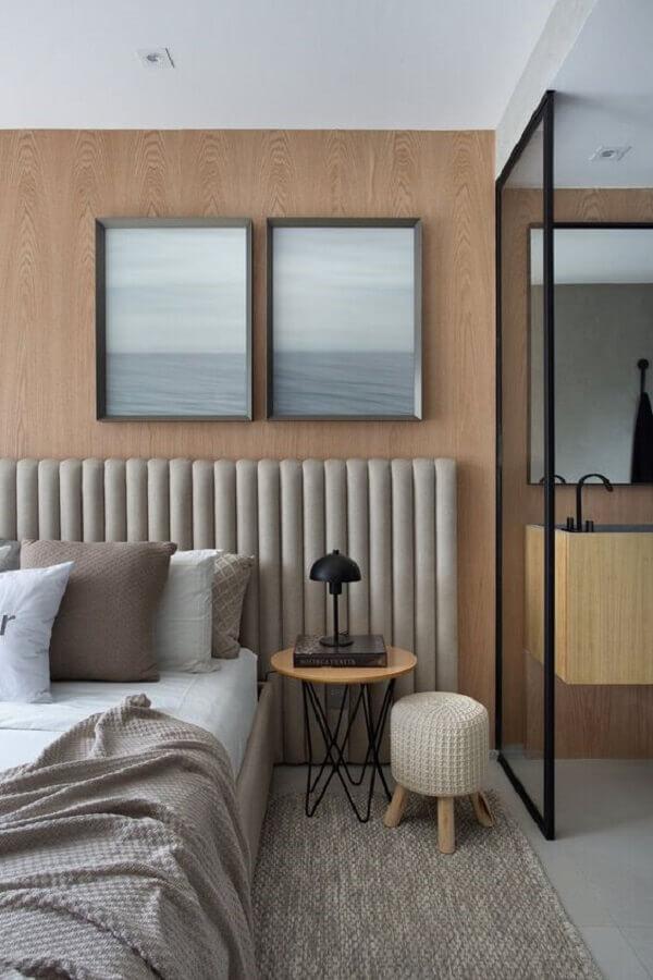 quarto moderno decorado com cabeceira estofada cinza em parede com revestimento de madeira  Foto Studio Roca