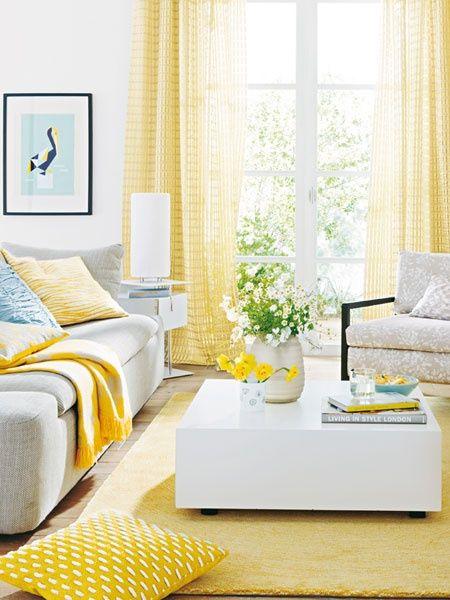 Sala amarelo pastel nas cortinas e manta do sofá