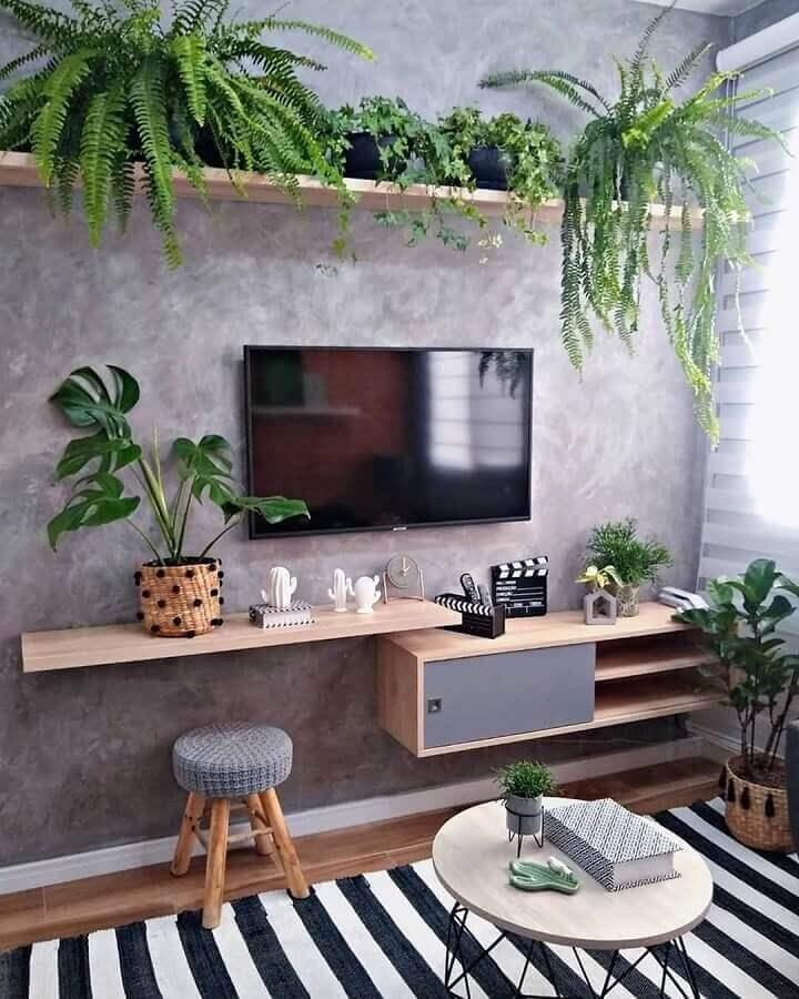 sala com parede de cimento queimado decorada com prateleira para plantas de madeira  Foto Revestindo a Casa