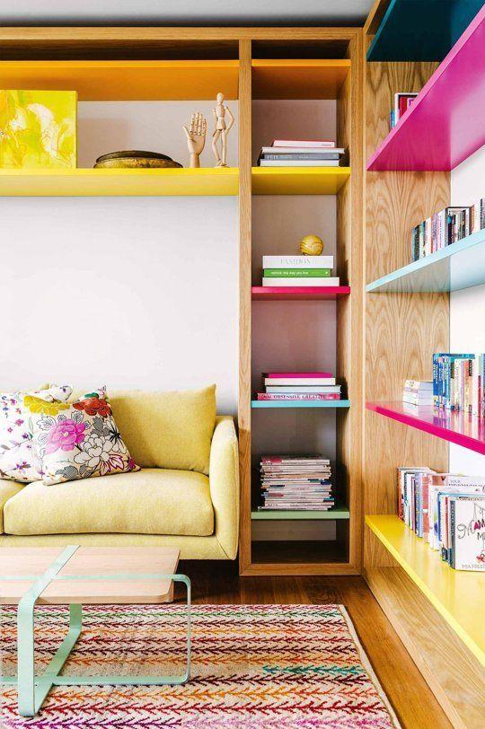 Sala com sofá amarelo pastel e estante colorida