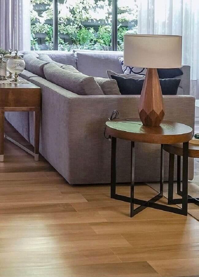 sala de estar decorada com sofá cinza e mesa de canto redonda de madeira e ferro Foto Archtrends