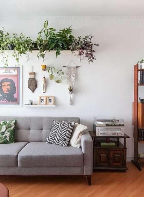 sala de estar decorada com sofá cinza e prateleira para plantas  Foto Histórias de Casa